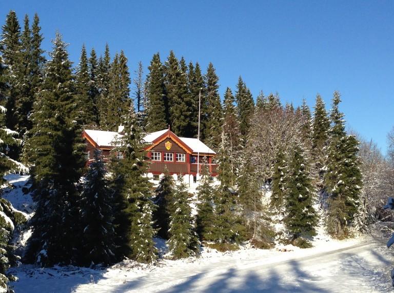 En hytte på fjellet i skogen, med snø rundt.